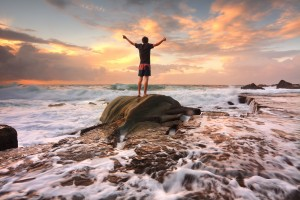 Teen boy stands on a rock among turbulent ocean seas and fast flowing water at sunrise. Worship praise zest adventure solitude finding peace among lifes turbulent times. Overcoming adversity.